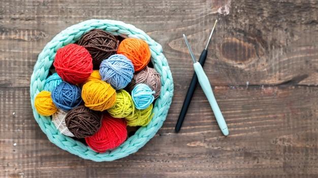 Bolas de lã multicoloridas dentro e perto do sofá de tricô