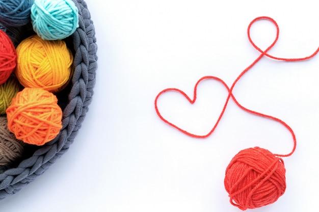 Bolas de lã multicoloridas no sofá de tricô e uma bola vermelha fazendo um coração. vista do topo