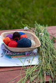 Bolas de lã para tricô em uma mesa de madeira, tricô em bordado da natureza no jardim