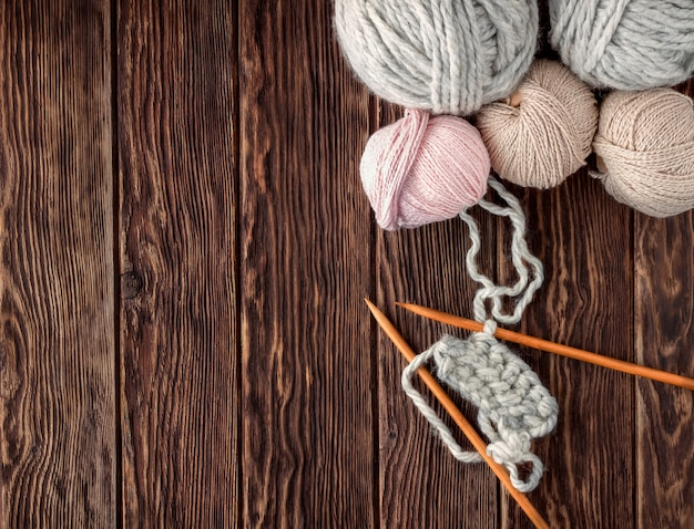 Bolas de linha e agulhas de tricô em um fundo de madeira. estilo rústico.