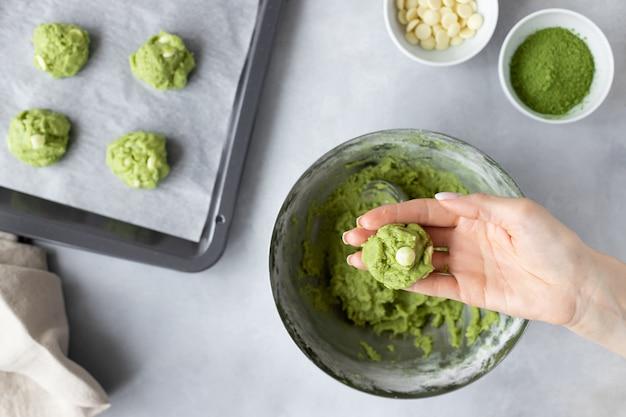 Bolas de massa de biscoito de chá verde matcha em mão feminina