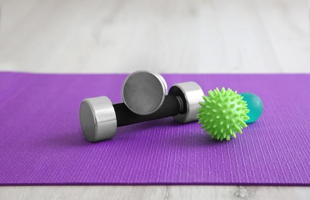 Bolas de massagem e halteres no tapete