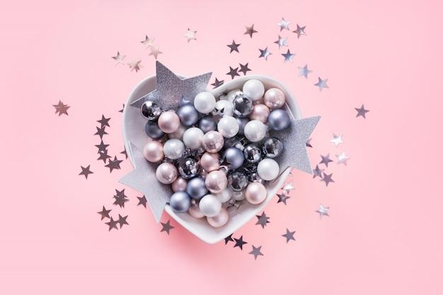 Bolas de natal brancas, rosa, cinza em forma de coração na rosa