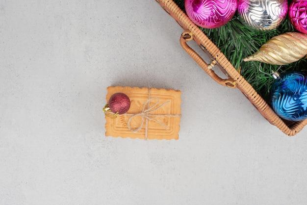 Bolas de natal coloridas na cesta com biscoitos na corda.