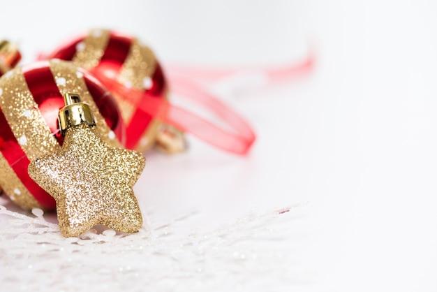 Bolas de natal com estrela dourada, pinhas e floco de neve em abstrato.