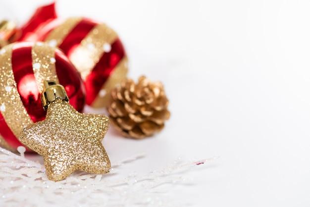 Bolas de natal com estrela dourada, pinhas e floco de neve em fundo branco.