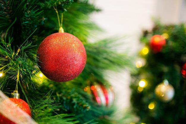 Bolas de natal de glitter vermelho em um abeto com luzes amarelas sobre fundo. copyspace.