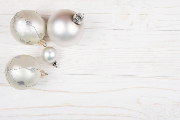 Bolas de natal de uma cor prata sobre um fundo de madeira
