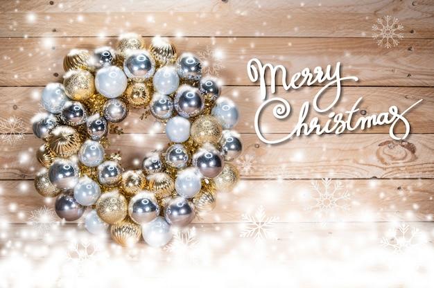 Bolas de natal dourada com brilho nevando no chão de madeira
