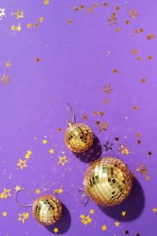 Bolas de natal douradas com estrelas brilhantes sobre fundo roxo
