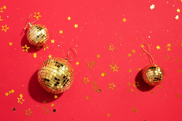 Bolas de natal douradas com estrelas brilhantes sobre fundo vermelho
