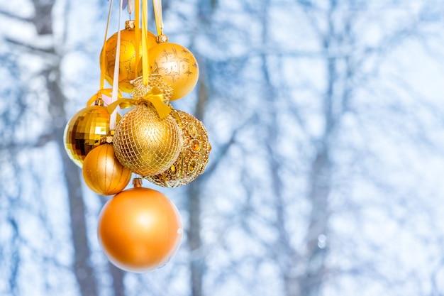 Bolas de natal douradas no fundo das árvores fora da janela no inverno_
