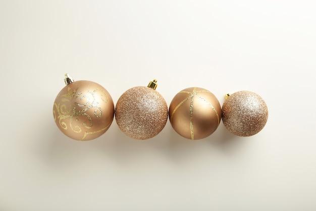 Bolas de natal douradas sobre fundo branco, vista superior, plana leiga. composição de ano novo