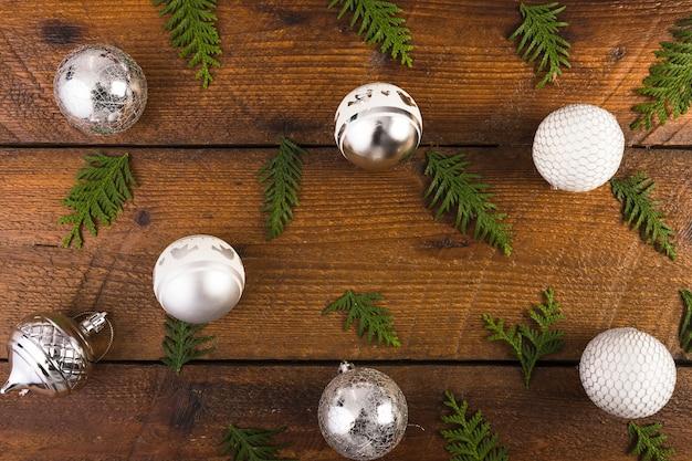 Bolas de natal e galhos de coníferas na placa de madeira