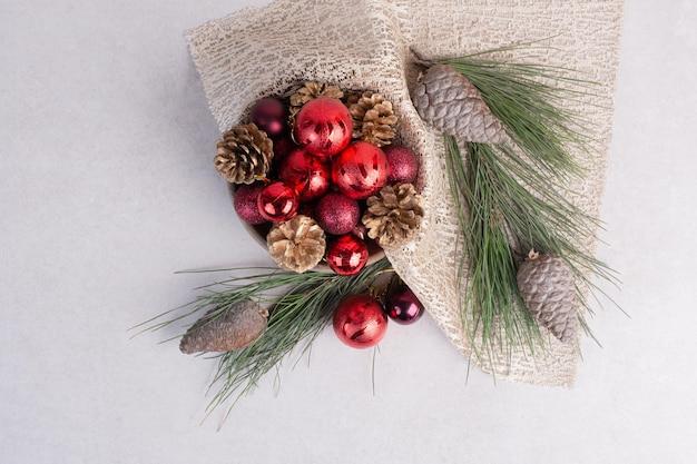 Bolas de natal e pinha na mesa branca.
