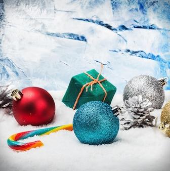 Bolas de natal e presentes na neve a janela congelada