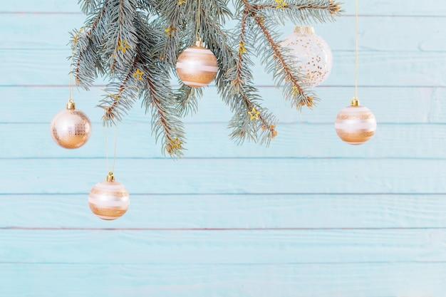 Bolas de natal em galhos de pinheiro em fundo azul de madeira