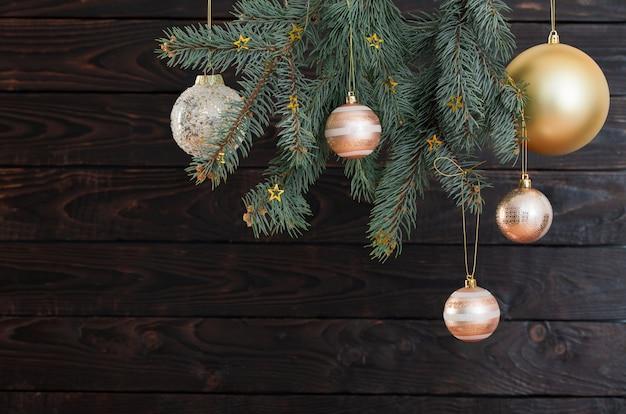 Bolas de natal em galhos de pinheiro em fundo escuro de madeira