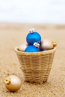Bolas de natal em uma cesta na costa arenosa do oceano