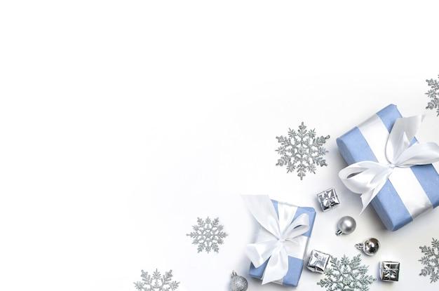 Bolas de natal, enfeites de prata e dois presentes em um fundo branco