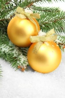 Bolas de natal na árvore do abeto com neve, isoladas no branco