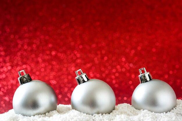 Bolas de natal prata na superfície de neve e glitter vermelho