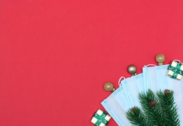 Bolas de natal, presentes, máscaras protetoras médicas, abeto com pinhas sobre fundo vermelho.