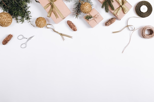 Bolas de natal, ramos de abeto, presente, fita, corda e tesoura em uma mesa branca, vista superior