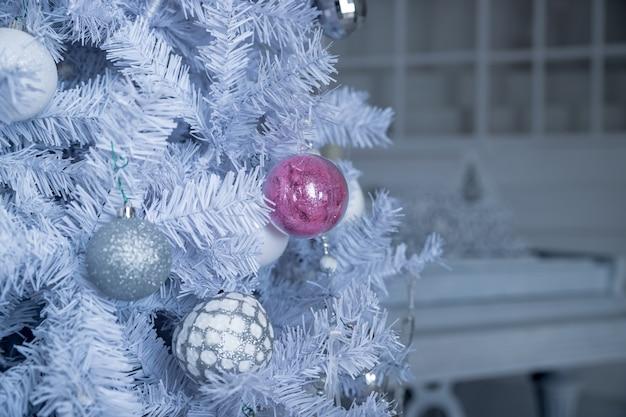 Bolas de natal, rosa e brancas pendurado no pinheiro