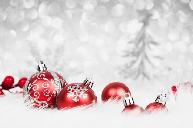 Bolas de natal vermelhas com decoração prateada na neve