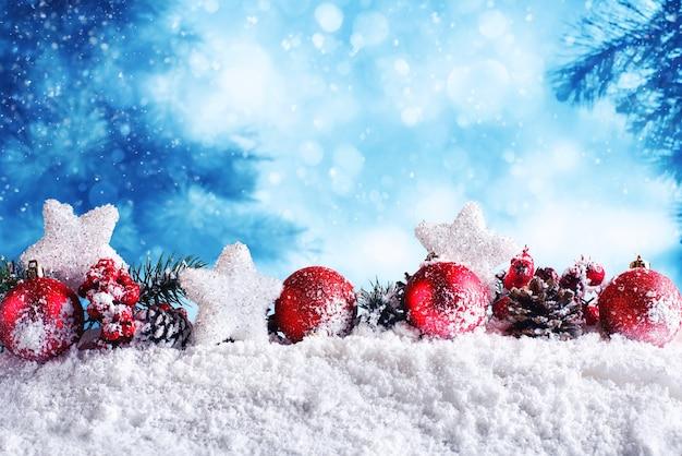Bolas de natal vermelhas com estrelas e guirlandas na neve