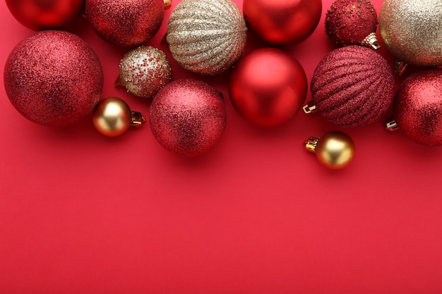 Bolas de natal vermelhas e douradas sobre um fundo vermelho