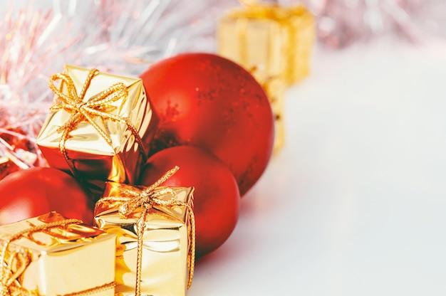 Bolas de natal vermelhas e presentes em caixas douradas.