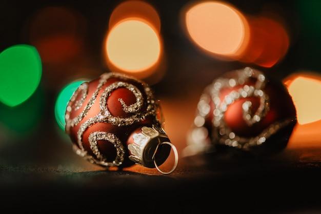 Bolas de natal vermelhas em guirlanda escura iluminadas