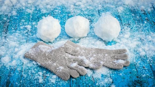 Bolas de neve e luvas em uma superfície de madeira pintada de azul coberta de neve