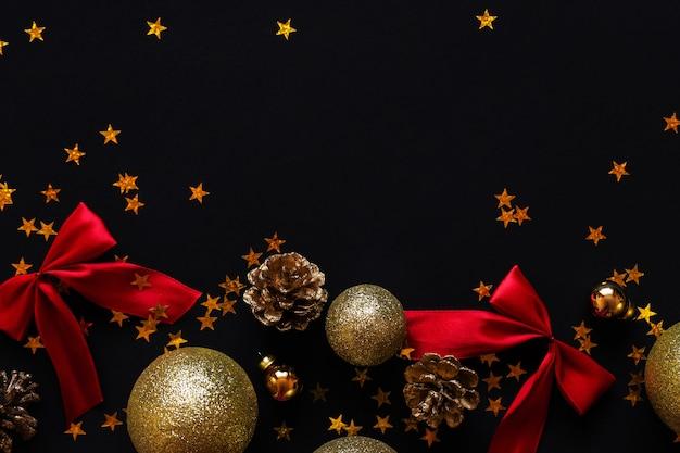 Bolas de ouro e cones com laços vermelhos em um fundo preto. layout das decorações de ano novo.