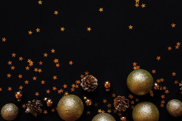 Bolas de ouro e cones em um fundo preto. layout das decorações de ano novo.