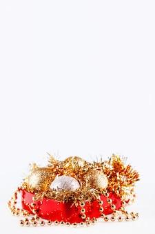 Bolas de ouro e prata em caixa com enfeites e miçangas. natal e decorações em caixa vermelha no branco.