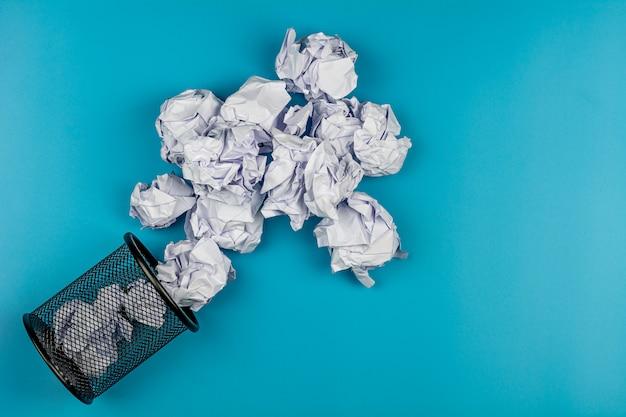 Bolas de papel amarrotadas brancas que rolam fora de um balde do lixo preto no fundo azul.