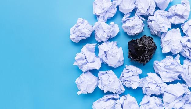 Bolas de papel amassadas brancas e pretas sobre um fundo azul.