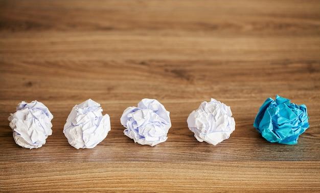 Bolas de papel amassadas na superfície da madeira