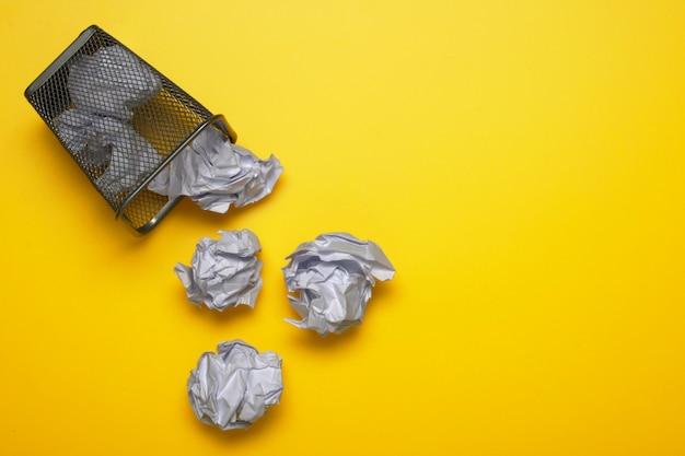Bolas de papel amassado branco com uma lata de lixo. cesta de metal. copie o espaço para o texto.