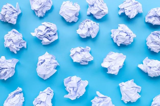 Bolas de papel amassado branco sobre um fundo azul.
