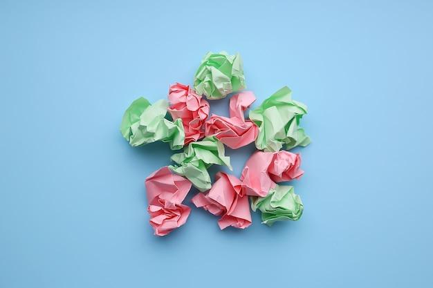 Bolas de papel amassado multicoloridas sobre um fundo azul.