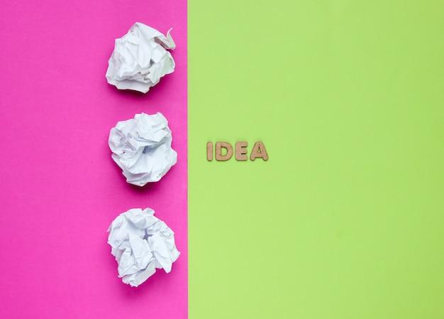 Bolas de papel amassado na superfície colorida com idéia de palavra.