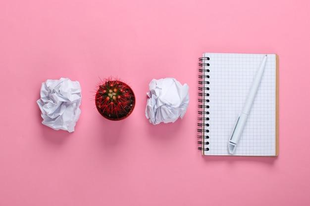 Bolas de papel amassado, pote de cacto e bloco de notas em pastel rosa. espaço de trabalho