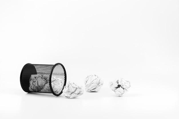 Bolas de papel branco e cesta caída no fundo branco