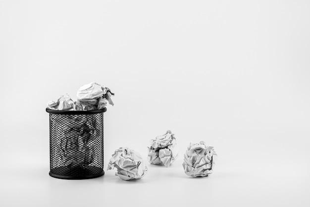 Bolas de papel branco e cesta em fundo branco