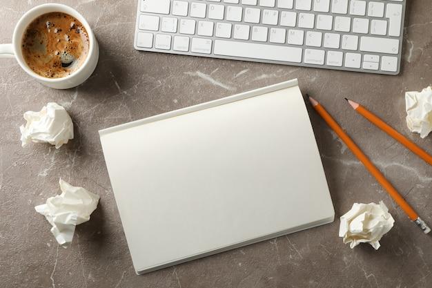 Bolas de papel, caderno, xícara de café, teclado e lápis sobre fundo cinza, vista superior