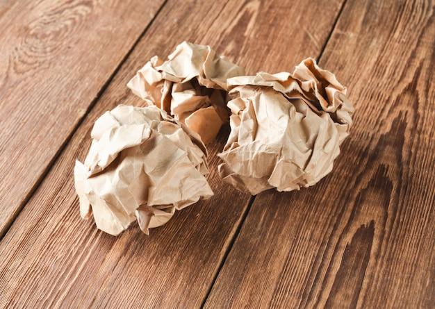 Bolas de papel velho amassado em uma mesa de madeira. o conceito de idéias inapropriadas e gastas.